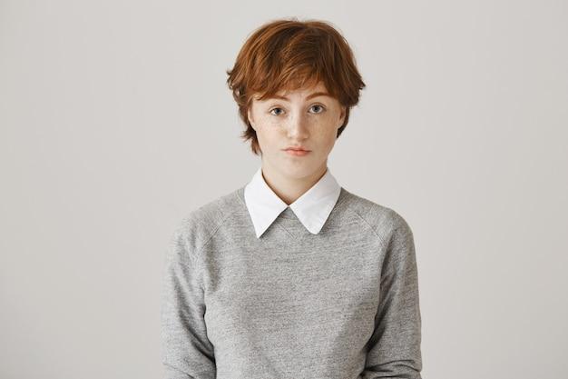 Ragazza rossa cupa con taglio di capelli corto in posa contro il muro bianco