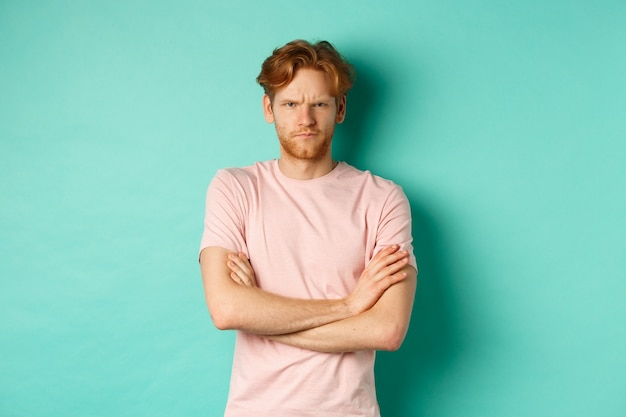 Gloomy redhead guy feeling offended, frowning upser with arms crossed on chest, looking insulted and sulking, standing over mint background