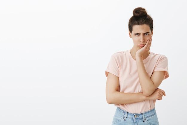 Мрачная грустная молодая стильная женщина позирует у белой стены