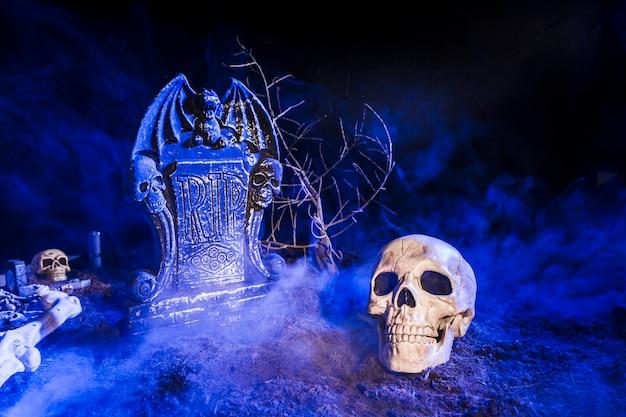 Cranio triste disposto vicino alla lapide in nebbia su terra