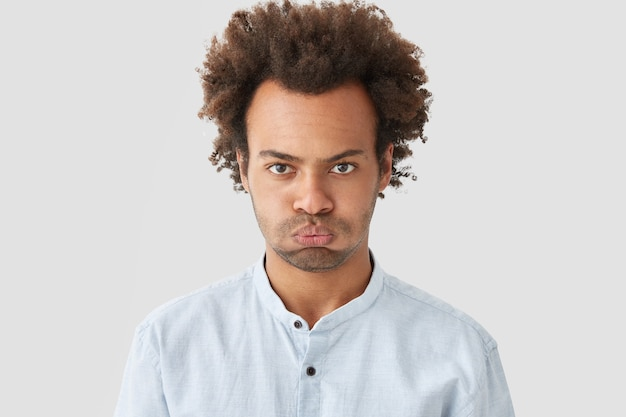 Gloomy sullen man with curly hair, has stubble, displeased expression, expresses negative emotions, dressed in white shirt