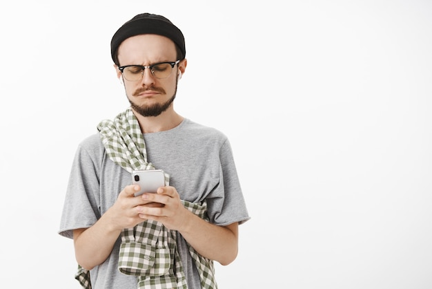 Gloomy unhappy and displeased handsome young bearded guy in glasses black beanie and checked shirt crossed on chest frowning making sad smile while staring with regret at smartphone screen