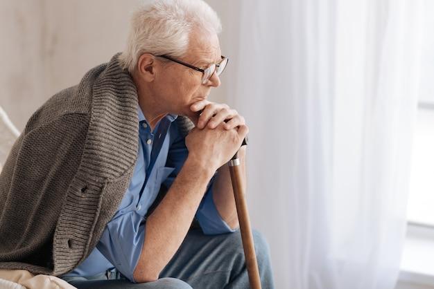 Мрачный несчастный пожилой человек, опирающийся на трость и думая о жизни, находясь в депрессии