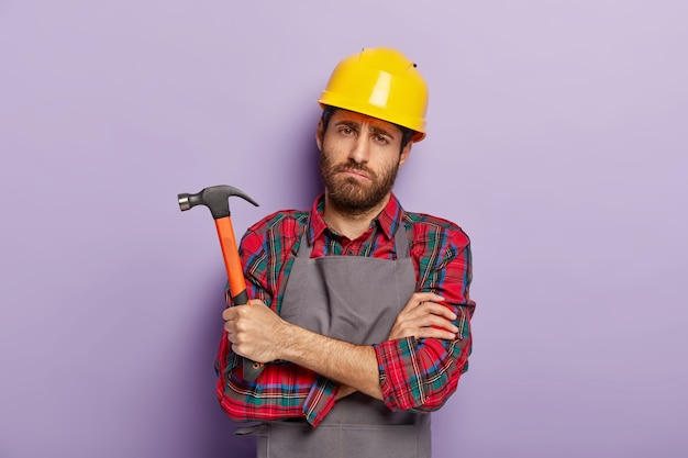 憂鬱な不幸な男性の修理工は、悲しそうな疲れた表情をしていて、手を組んで、ハンマーを手に持って、修理と手作業の後の疲労感があり、特別なユニフォームを着ています。手作り、ハンマー、建物。
