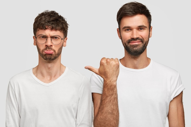 Gloomy unshaven young man model with grumpy expression, being in low spirit, stands near best man companion, wear casual white t shirts, express different emotions