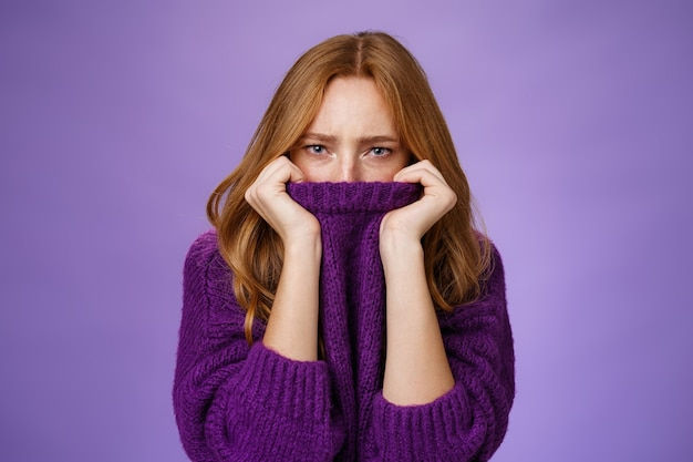 Gloomy upset redhead girlfriend pulling collar of purple sweater on nose, frowning and squinting offended, being aggrieved and resent, sulking moody and displeased over violet background.