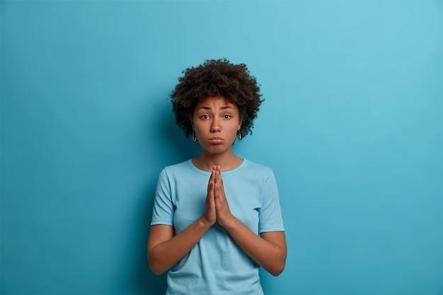 アフロの髪をした憂鬱な動揺した女性は、手のひらを押し付けて祈り続け、青い壁に供給し、あなたの助けを必要とし、好意を求め、カジュアルなtシャツを着て、無邪気な表情を作ります