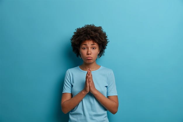Gloomy upset woman with afro hair keeps palms pressed together in pray, supplicates over blue wall, needs your help, begs for favor, wears casual t shirt, makes innocent face expression