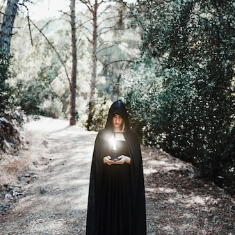 Gloomy woman in cape holding burning candle in sunny forest