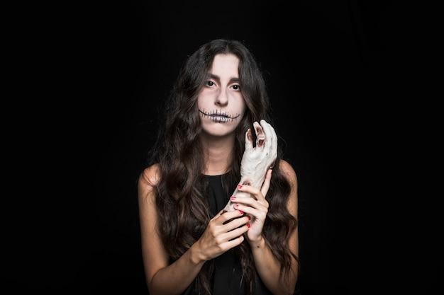 Gloomy woman holding dead hand