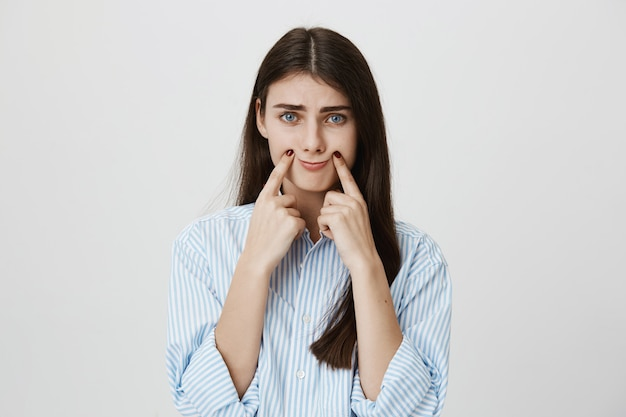 Gloomy woman making smile with fingers on corner of lips