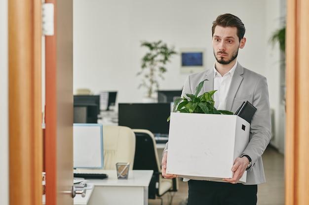 해고 후 사무실을 떠나는 동안 물건 상자를 들고 우울한 젊은 수염 난된 남자