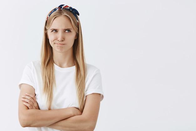 Мрачная молодая блондинка позирует у белой стены
