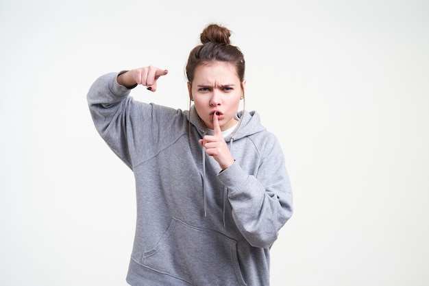 흰색 배경에 서있는 카메라를 심각하게 보여주는 동안 그녀의 입에 집게 손가락을 유지하는 자연 화장과 우울한 젊은 갈색 머리 여자