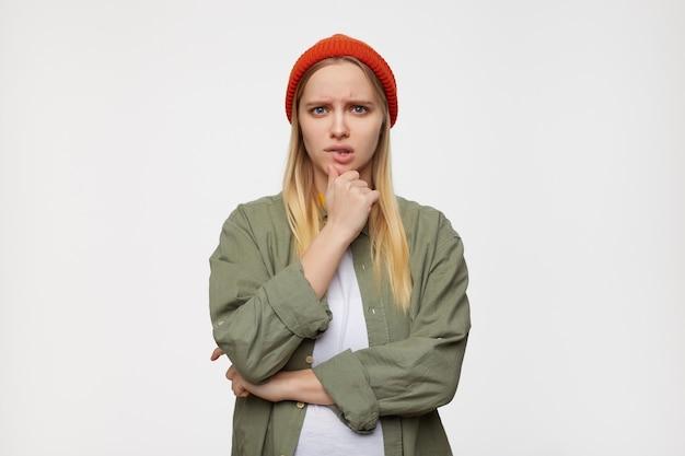 Cupa giovane signora dai capelli bianchi piuttosto lunghi che tiene il mento con la mano alzata mentre guarda pensieroso, isolato sul blu