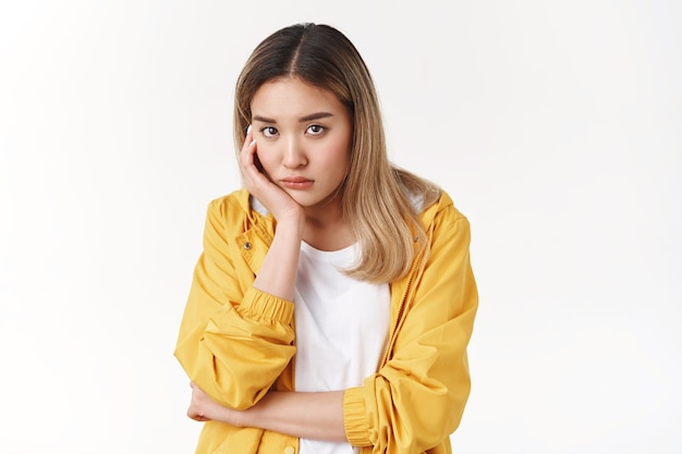 Gloomy young sad asian blond girl sighing upset stoop look from under forehead lonely unhappy lean palm bored feel regret sadness moody expression standing white wall pessimistic