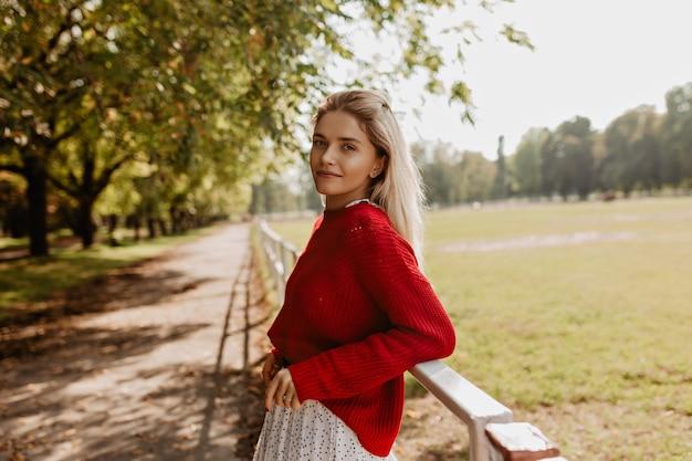 公園でリラックスして立っている栄光のブロンドの女性。素敵な秋の景色を楽しんでいる素敵な女の子。