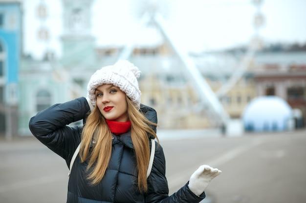 街歩きを楽しんで、ニット帽をかぶった赤い口紅を持つ栄光のブロンドの女性。テキスト用のスペース