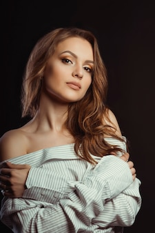 Glorious brunette woman posing in men's shirt on a black background