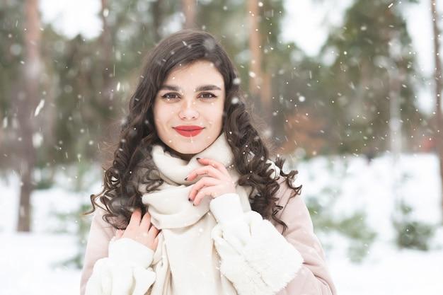 長い髪の栄光のブルネットの女性は雪の天気でコートを着ています。テキスト用のスペース