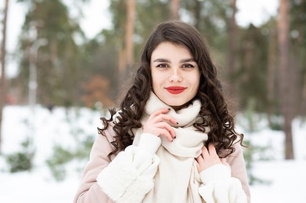 長い髪の栄光のブルネットの女性は冬にコートを着ています。テキスト用のスペース