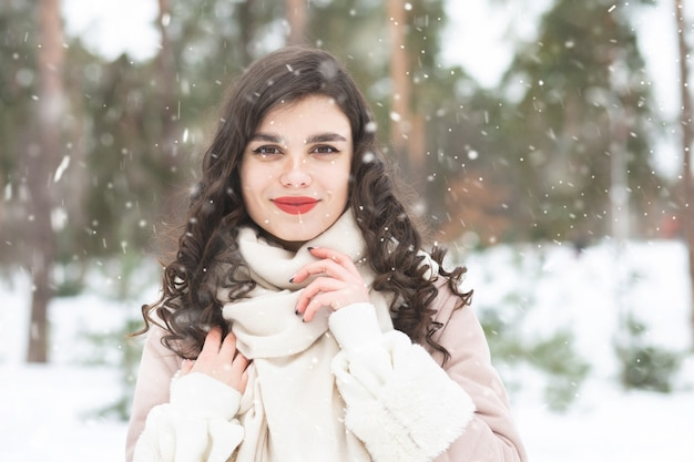 Glorious brunette woman with long hair wears coat in snowy weather. space for text