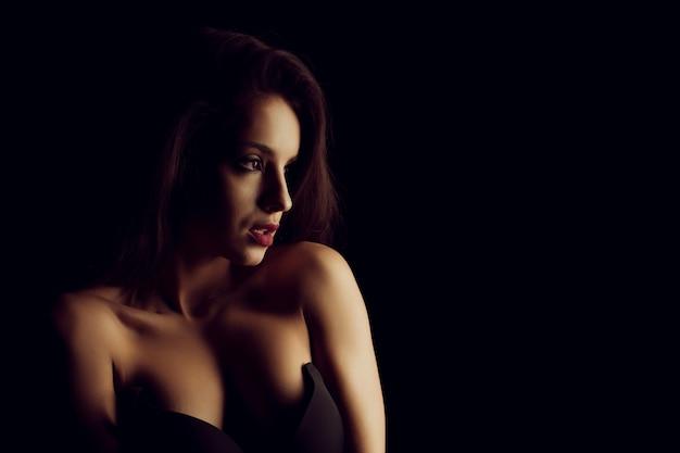 Славная брюнетка молодая женщина в черном бюстгальтере с обнаженными плечами позирует в тени