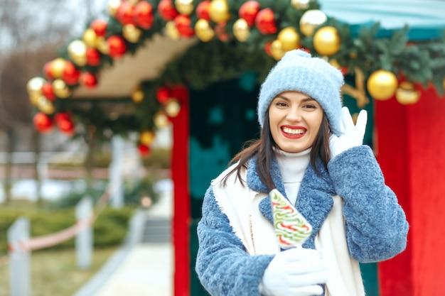 クリスマスマーケットでキャンディーを保持している栄光の笑顔の女性。空のスペース