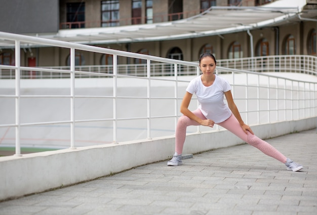 Glorious tanned athletic girl wearing sport apparel doing stretching workout at the stadium. space for text