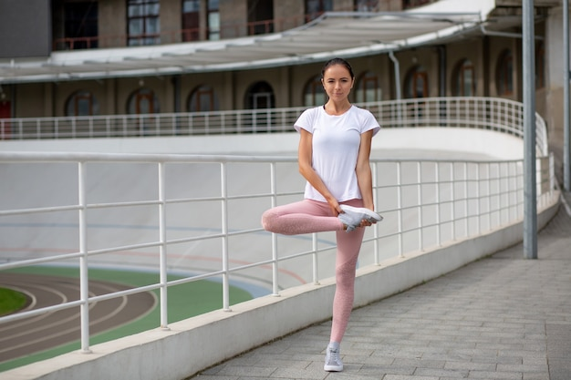 Glorious tanned athletic woman wearing sport apparel doing stretching workout at the stadium. space for text