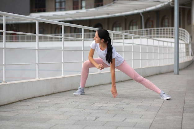 Glorious tanned athletic woman wearing sport clothes doing stretching workout at the stadium. space for text