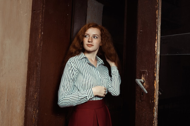 古いドアの近くに立っている縞模様のシャツと赤いスカートの栄光の若い赤い髪のモデル