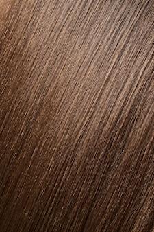 광택 있는 갈색 머리 질감, 배경입니다. 긴 직선 여성의 머리를 가까이에서 볼 수 있습니다. 헤어 케어 개념입니다.