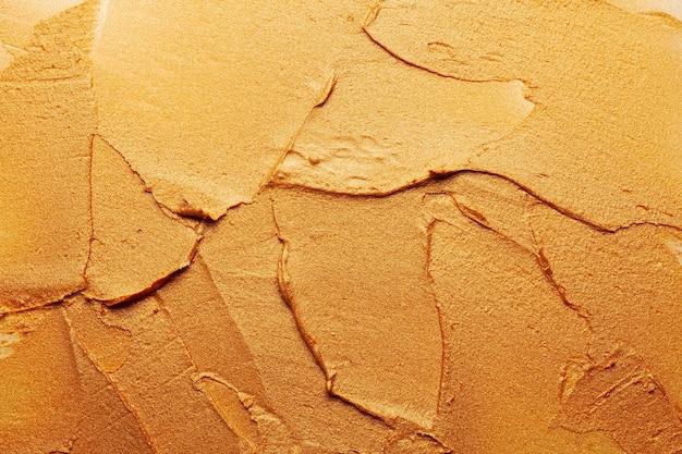 光沢のあるゴールドの口紅の背景テクスチャが汚れています