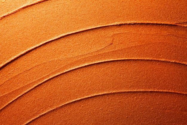 光沢のあるゴールデンオレンジの口紅の背景のテクスチャが汚れています
