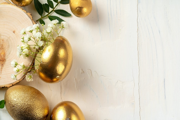 Glossy golden painted eggs with floral branches