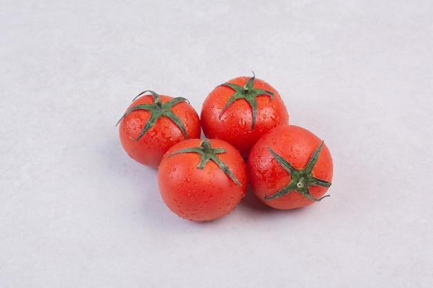 흰색 표면에 광택있는 빨간 토마토