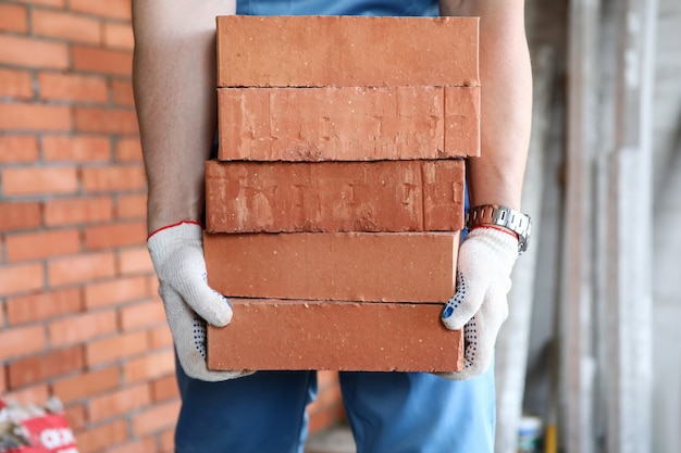 Gloved builder manually carries brick construction. building bricks are used for exterior and interior use. appearance brick walls is presentable. brick used construction walls, pillars and arches