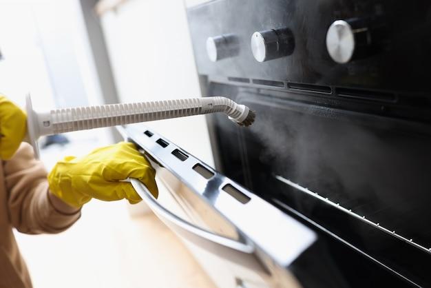 自宅のクローズアップで蒸し器と手袋をはめたクリーナー洗濯オーブン