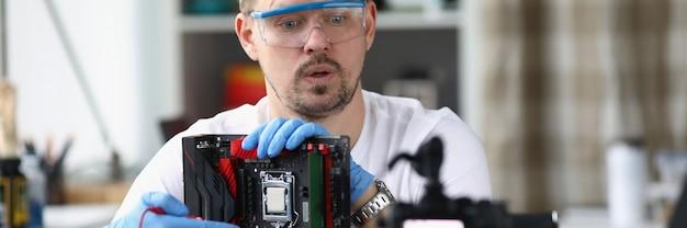 Мастер в перчатках держит разобранное компьютерное оборудование и показывает его желающим