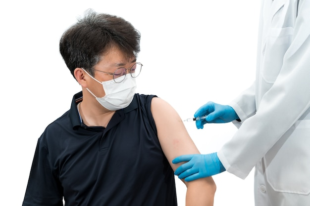 A gloved doctor holding a syringe gives a vaccine injection to an asian middle-aged male patient wearing a medical mask.