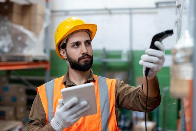 Инженер в перчатках или менеджер по логистике, просматривающий упакованные товары на складе