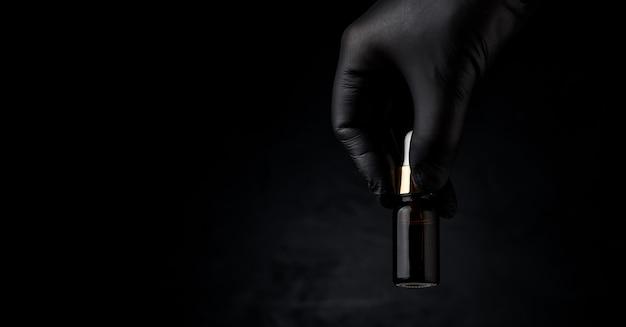 의료 전문가의 장갑을 낀 손은 콜라겐 병을 손에 들고 있습니다.