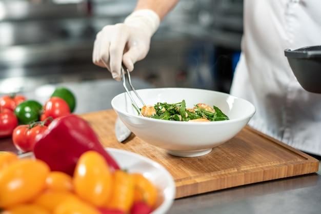 Рука в перчатке молодого шеф-повара с вилкой кладет приготовленную еду в белую керамическую миску, стоящую на деревянной доске в окружении свежих овощей