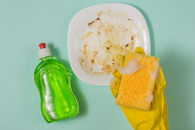 A gloved hand with a foam sponge and detergent on the background of a dirty plate