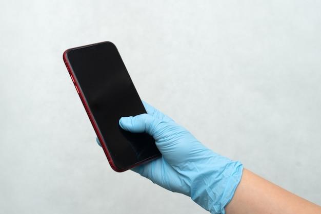 Руки в перчатках держат телефон