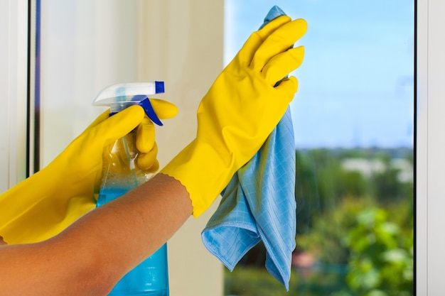 Gloved hands cleaning window with rag