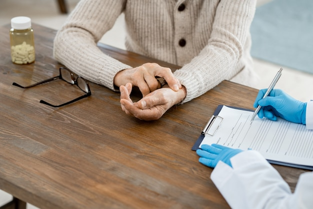 Gloved hands of female doctor with pen over medical paper making prescriptions for sick senior man sitting near by and touching his pulse