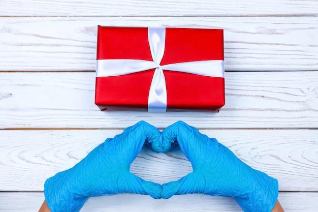 Руки в перчатках держат красную подарочную коробку с лентой на деревянном фоне