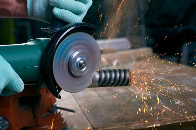 Gloved hands hold an angle grinder and cut the pipe, many sparks fly on the workbench
